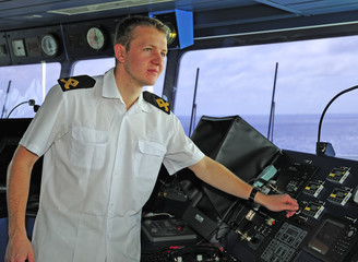 Navigation officer works with a navigation chart