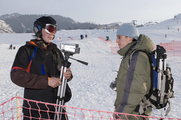 Couple of photographers after sports competition in winter mount