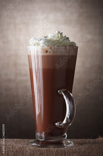 Hot Chocolate with cream in Tall Glass on brown rustic backgroun