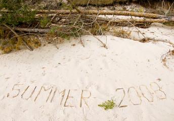 """Inscription """"Summer 2008"""" on beach sand near pines"""