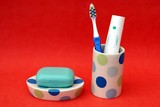 tablet of soap on dish. toothpaste & toothbrush in container poster