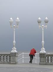 Hombre mirando al mar y farolas