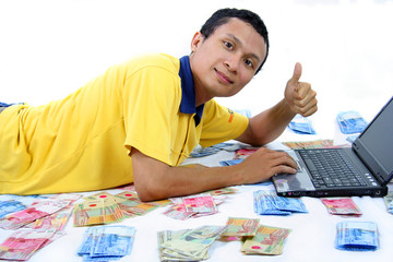 man play laptop with smile and money around him
