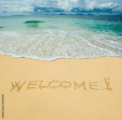 In de dag Golven welcome written in a sandy tropical beach