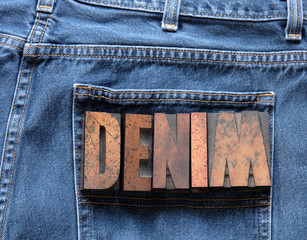 the word 'denim' in wood type on a worn pair of jeans