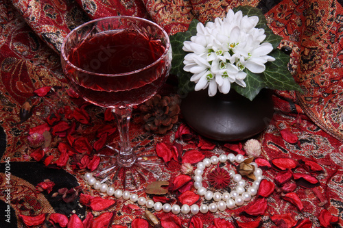 Still life with wine, flowers and pearls