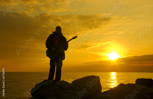 lonely guitarist on the evening beach