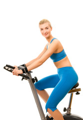 Beautiful young woman on exercise bicycle over white background