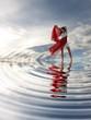 Im Wasser stehende Frau mit Spiegelung der Wolken