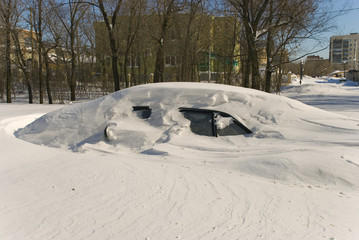 Car covered with snow in winter blizzard snowdrift