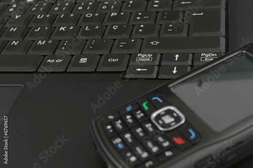 Cellphone isolated over laptop keyboard