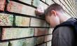 Leinwanddruck Bild - upset boy against a wall