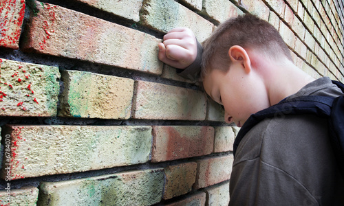upset boy against a wall - 6784070