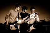Portrait of young rock band performing - monochrome poster