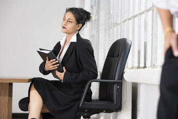View of a woman holding files in an office.