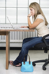Side view of a teen girl working on a laptop.