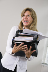 A business woman holding files.
