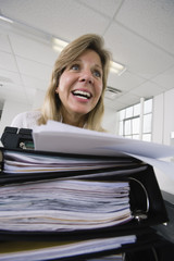 A frustrated business woman in front of files.