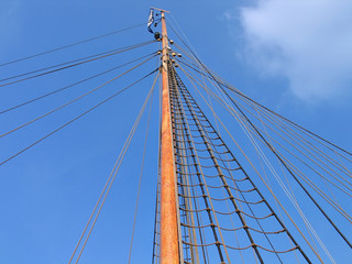 Wooden mast of a boat with clear blue sky behind