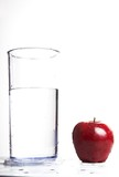 Apple next to a glass of water on white