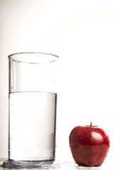 A glass of water next to a red delicious apple