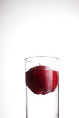 A red delicious apple floating in a glass of water