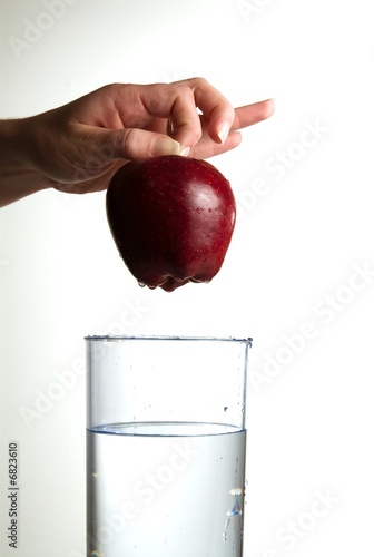 A hand dropping an apple in glass water