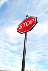 Stop sign on a blue sky from below.
