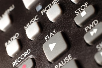 A closeup of a remote control focusing on the play button.