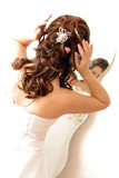 Woman adjusting her hair in a mirror poster