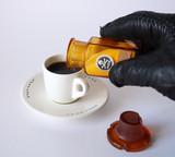 Hand in black leather glove strewed poison in cup of coffee poster