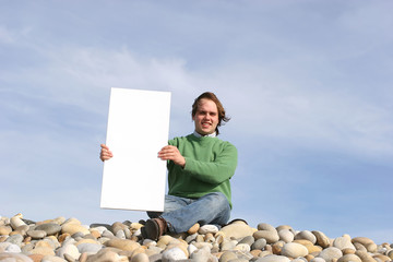 Young Man Holding White Card at the beach
