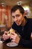 Young man eating burger in fast food restaurant. Shallow DOF. poster
