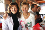 Two happy mature women at party in restaurant poster