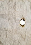 burnt hole in wrinkled paper poster