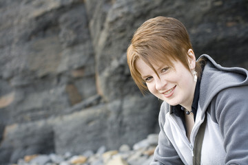 Smiling girl on a rocky beach