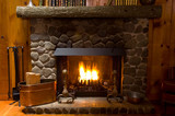 Fototapety close-up of stone fireplace in log cabin with blazing fire
