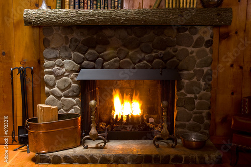 close-up of stone fireplace in log cabin with blazing fire - 6923210