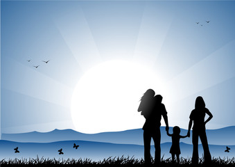 Family at sunset in a meadow