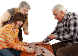 grandparents and granddaughter play dominoes on the table