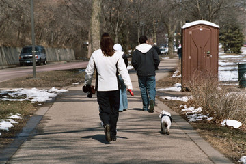 People walking along with dog in the park in early spring