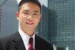 Young asian executive in front of office buildings