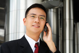 Young asian executive talking on handphone