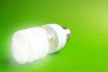 Compact fluorescent light bulb on green (green energy)