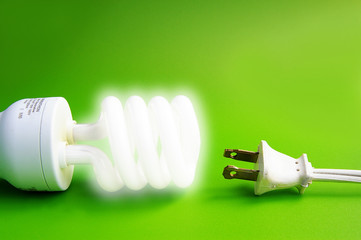 Glowing light bulb with power cord, on green