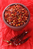 Hot Red Chilli Chillies crushed pepper in teracotta pot on red B poster