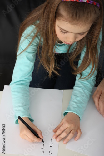 A small girl learning to write