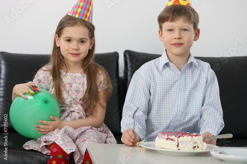 A brother and a sister with a birthday cake