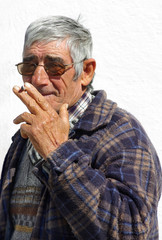 Old and happy man smokes a cigarette.