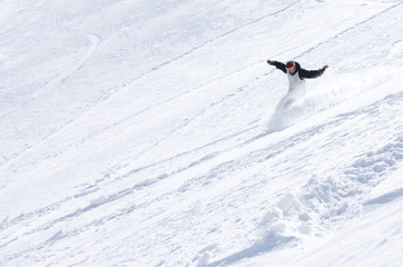 Male snowboarder sliding down the mountain